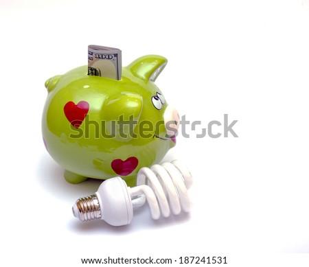 Piggy bank with a CF bulb near (smart energy)  - stock photo