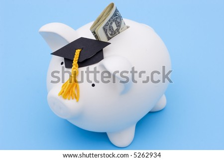 Piggy bank with a graduation cap on blue background - stock photo