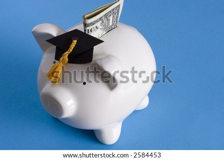 Piggy bank with a graduation cap with dollar bill - stock photo