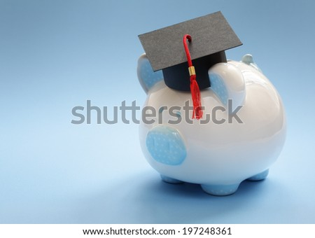Piggy bank with a graduation mortar board cap concept for the cost of a college education - stock photo
