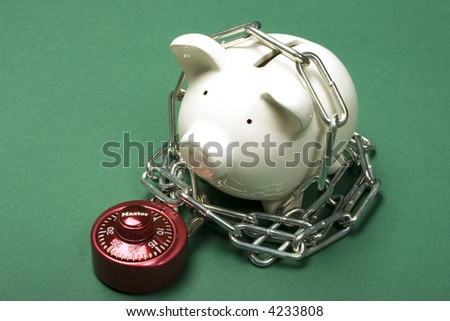Piggy bank with a red combination lock and chain - stock photo