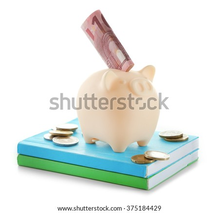 Piggy bank with banknote and coins on top of books isolated on white - stock photo