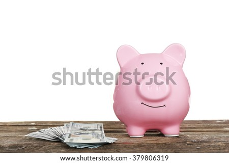 Piggy bank with banknotes on wooden table, isolated on white - stock photo