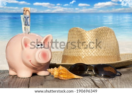 Piggy bank with banknotes, Seashells, Straw Hat and Sunglasses on Wooden Boards at the beach with much Copy Space for additional information