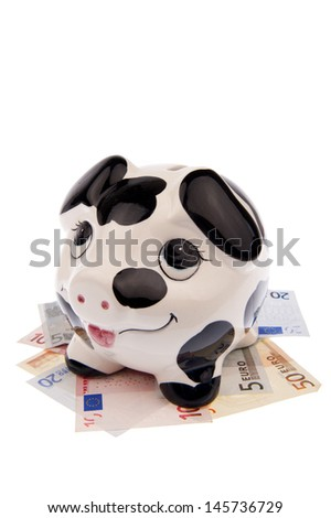 Piggy bank with black and white cow spots, looking upwards and standing in a bed of Euro banknotes and isolated in white background in portrait - stock photo