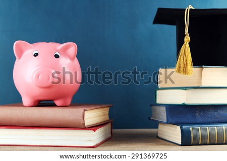 Piggy bank with books and Grad hat on blackboard background - stock photo