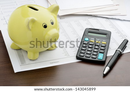 Piggy bank with calculator and business reports - stock photo