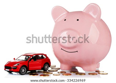 Piggy bank with car toy and coins around, isolated on white - stock photo