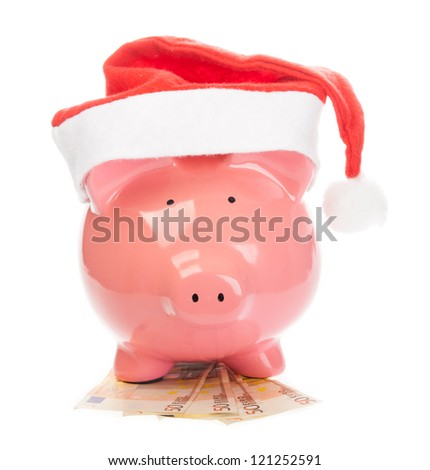 Piggy bank with christmas hat standing on euros. - stock photo