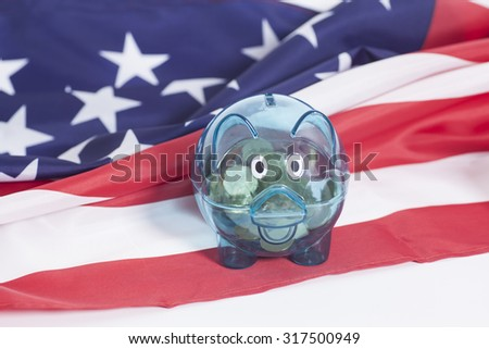 Piggy bank with  coins on American national flag,closeup