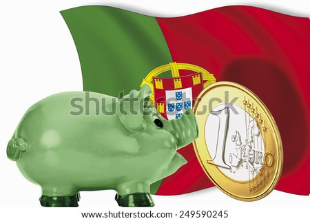 Piggy bank with 1 euro coin and portuguese flag - stock photo
