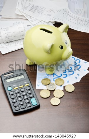 Piggy bank with euro money and calculator ready to pay the bills - stock photo