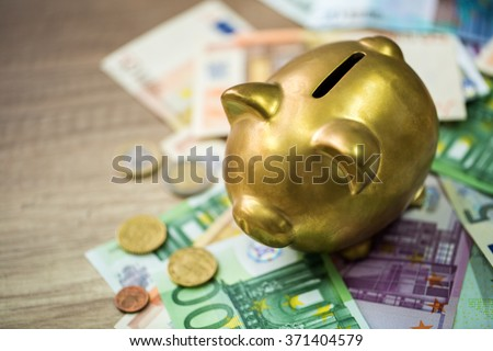 Piggy bank with euro on wooden table, finance concept - stock photo
