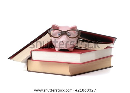piggy bank with eyeglasses on top of books isolated white background