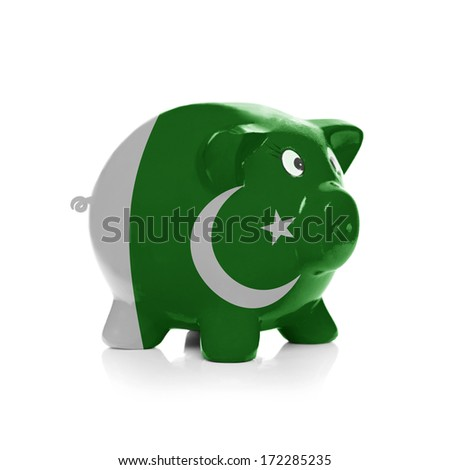 Piggy bank with flag coating over it isolated on white - Pakistan - stock photo