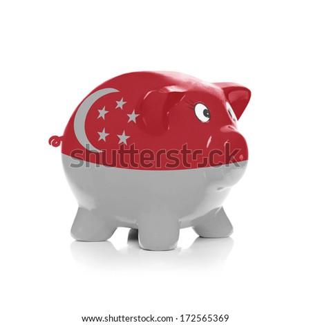 Piggy bank with flag coating over it isolated on white - Singapore - stock photo