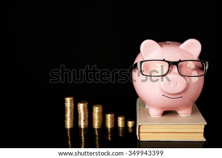 Piggy bank with glasses,coins and book on a black background - stock photo
