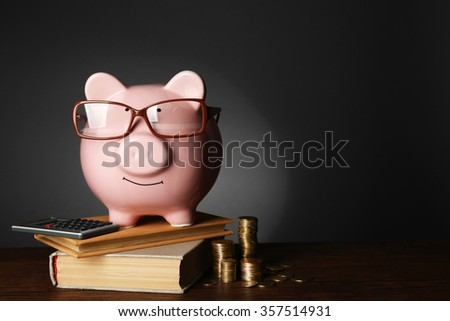 Piggy bank with glasses ,coins and books on table , gray background - stock photo