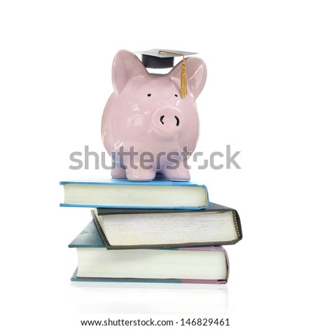 piggy bank with graduation cap on a pile of books                                - stock photo