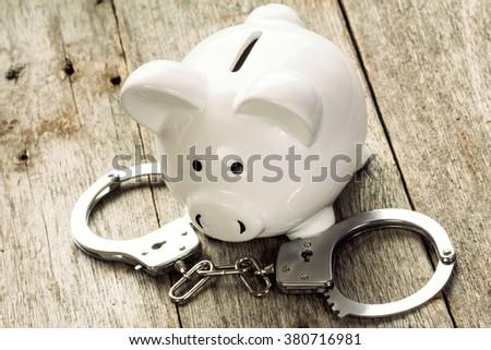 Piggy bank with handcuffs on old wooden background