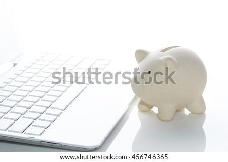 Piggy bank with laptop - stock photo