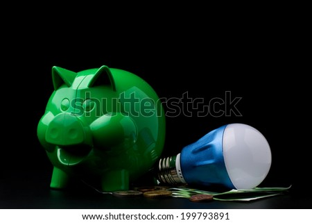 Piggy Bank with LED bulb on dark background with coins - stock photo