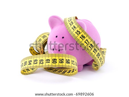 Piggy bank with measure tape - stock photo