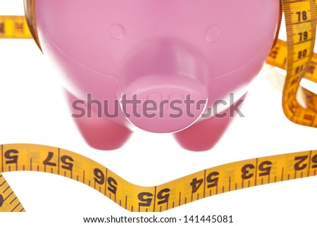 Piggy bank with measure tape in a macro image - stock photo