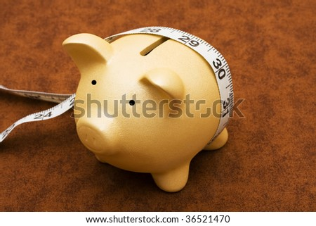 Piggy bank with measuring tape on a brown textured background, measuring your savings - stock photo