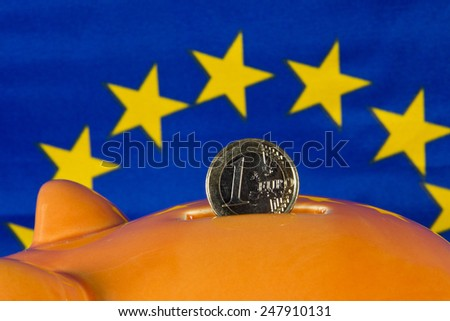 Piggy bank with one euro coin, EU flag in background - stock photo