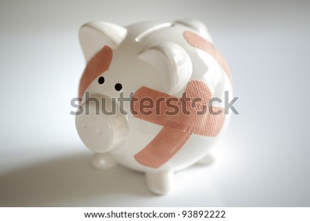 Piggy bank with plasters concept for financial crisis or economic depression - stock photo