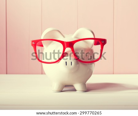 Piggy bank with red glasses on pink wooden wall - stock photo