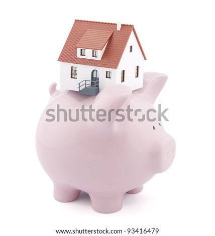 Piggy bank with small model house - stock photo