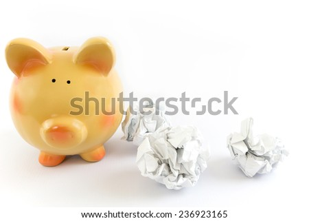 Piggy bank with some crumpled paper balls - stock photo
