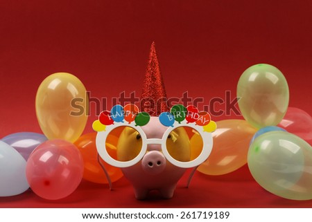 Piggy bank with sunglasses Happy birthday , party hat and multicolored party balloons on red background - stock photo