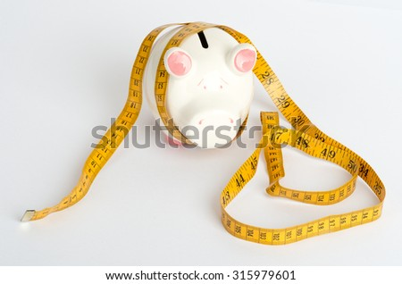 Piggy bank with tape measure on isolated white background, side view - stock photo