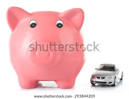 Piggy bank with toy car isolated on white - stock photo