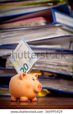 Piggy bank with twenty euro note over stack of office folders. Shallow depth of field - stock photo