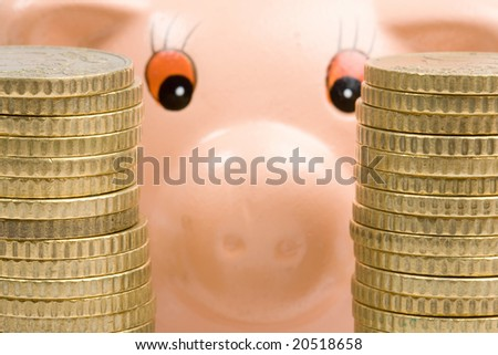 Piggy bank with two towers of coins-Shallow DOF- - stock photo