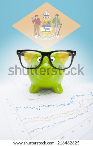 Piggy bank with US state flag on background - Delaware - stock photo