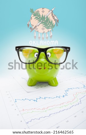 Piggy bank with US state flag on background - Oklahoma - stock photo