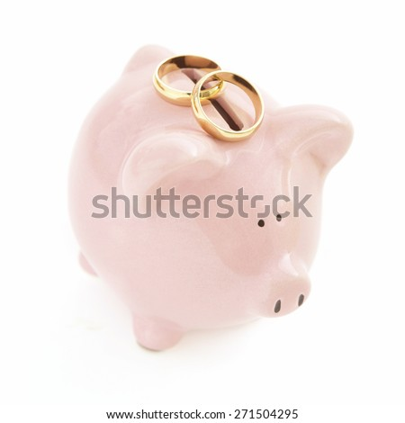 Piggy Bank with wedding rings on White Background - stock photo