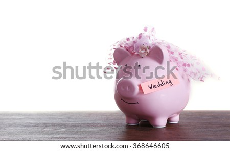 Piggy bank with wedding veil on wooden table, on white background - stock photo