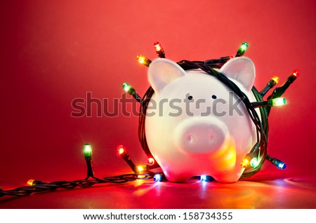 Piggy bank wrapped in Christmas string lights - stock photo