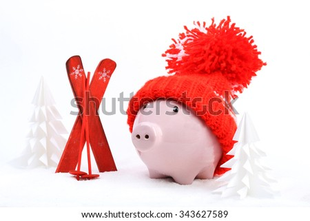 Piggy box with red hat with pompom standing next to red ski and ski sticks on snow and around are snowbound trees  - stock photo