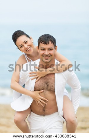 Piggyback. Young man carrying on shoulders his girlfriend. They look at camera smiling - stock photo