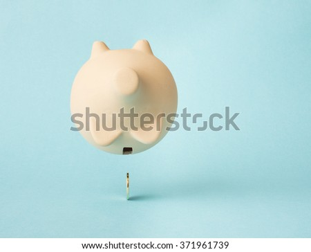 Piggybank floating in air upside down. The last golden coin have fallen out. Concept of saving money, financial crisis and economy. - stock photo