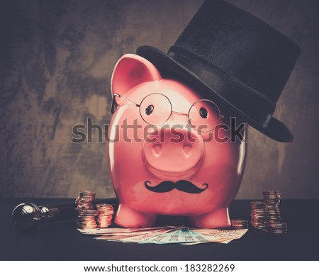 Piggybank in glasses and hat with pile of coins and banknotes  - stock photo