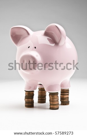 Piggybank placed on stacks of pennies - stock photo
