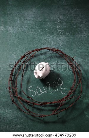 piggybank surruonded by the barbwire ,protect your saving - stock photo